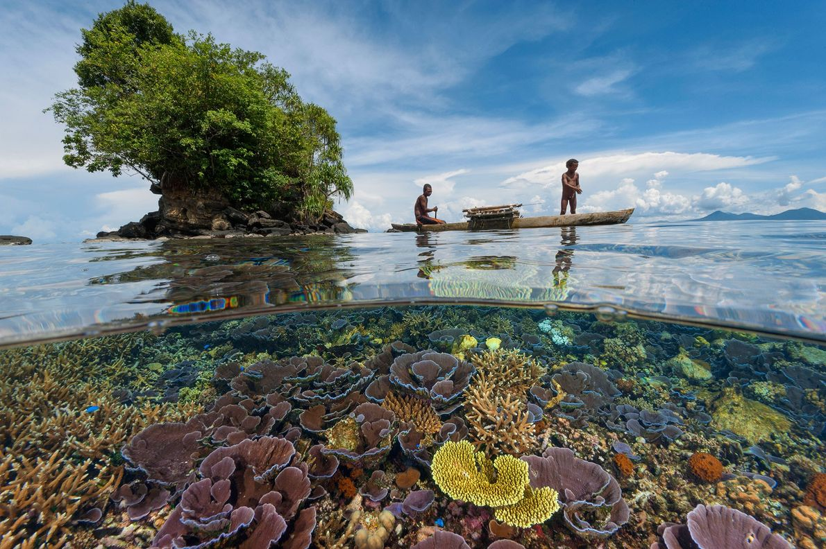 Father and son fisherman in a wooden outrigger glide over a shallow coral reef in the ...