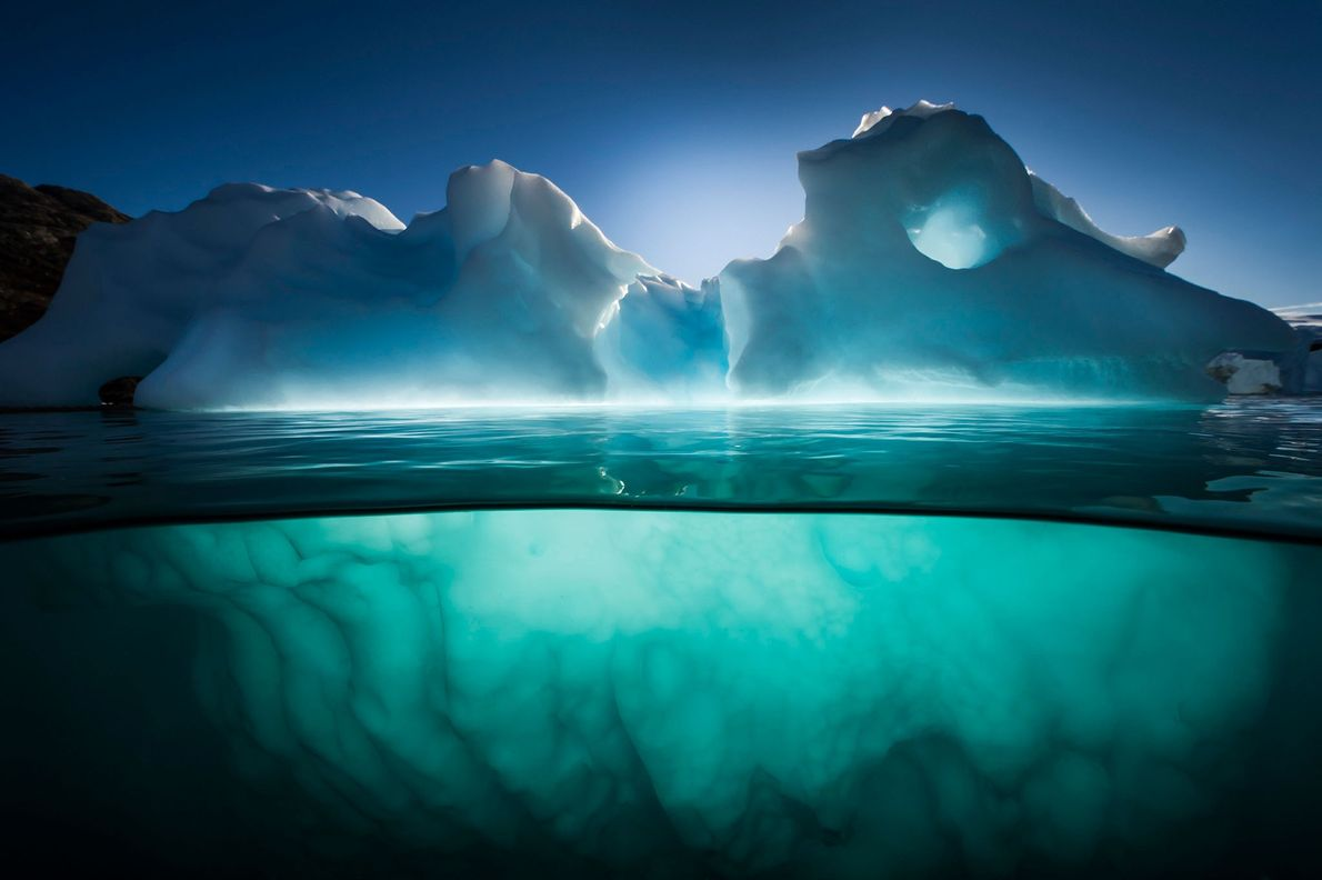 An iceberg glows in late afternoon light near Red Island in Scoresbysund Fjord, Greenland. Icebergs are ...