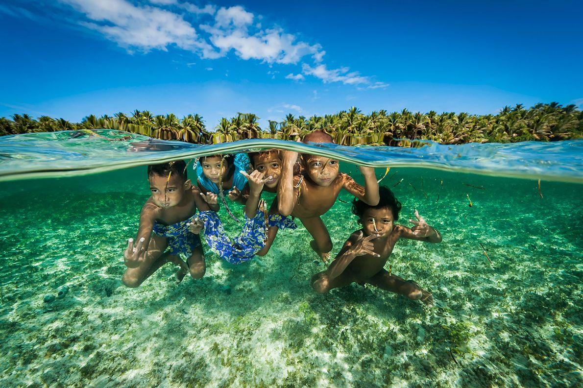 Descendants of the legendary Satawal Island navigators play in the warm waters of the Caroline Islands ...