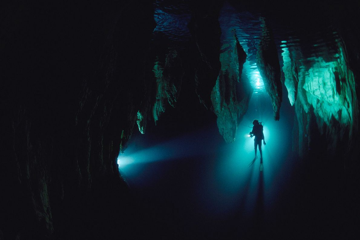 A diver is silhouetted in Chandelier Cave in Palau, Micronesia. Cave diving can be dangerous, but ...