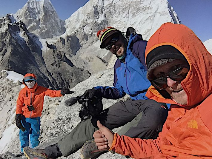 Conrad Anker (right) and Lama (left), along with cameraman Martin Hanslmayr (center), rest on the summit ...