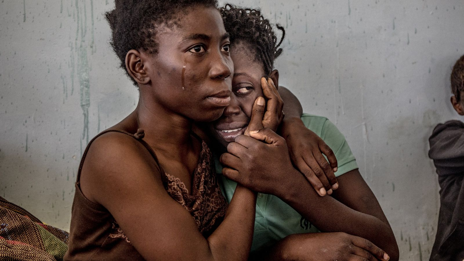 Nigerian migrants cry and embrace in a detention centre for refugees and migrants in Surman, Libya, ...