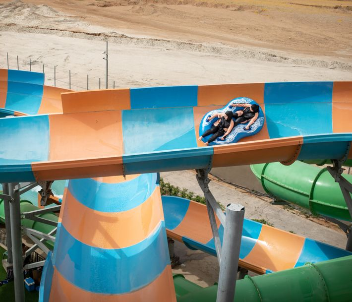 Girls enjoy a water slide in Jericho, surrounded by desert.