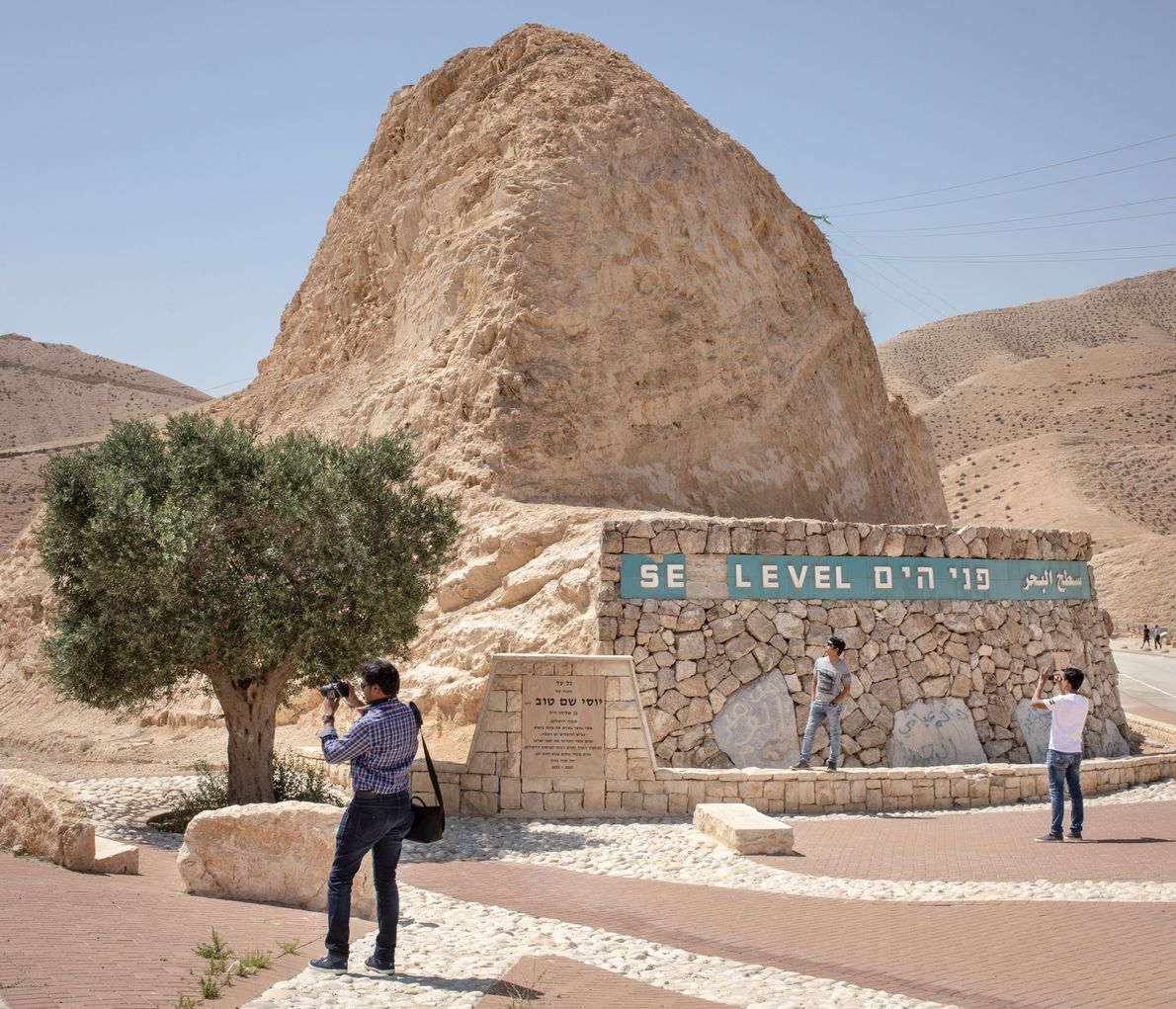 Tourists take pictures under the line that marks zero feet above sea level.