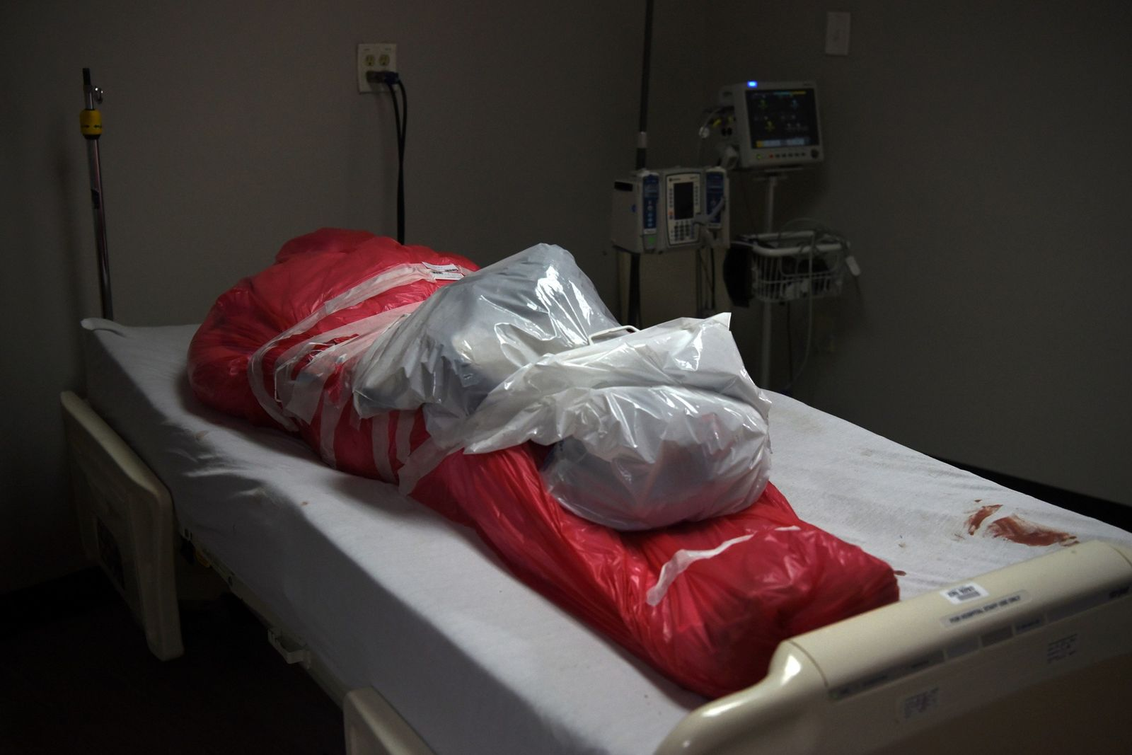 A man who died from coronavirus is seen wrapped in a body bag at the United ...