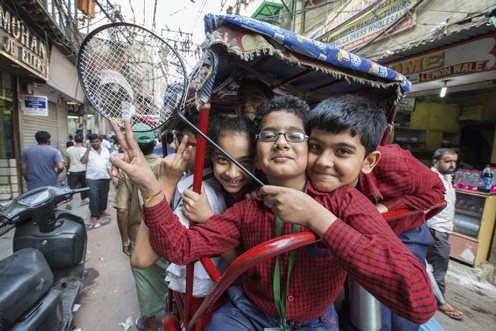 Kids riding in a tuk-tuk through Chandni Chowk neighbourhood.