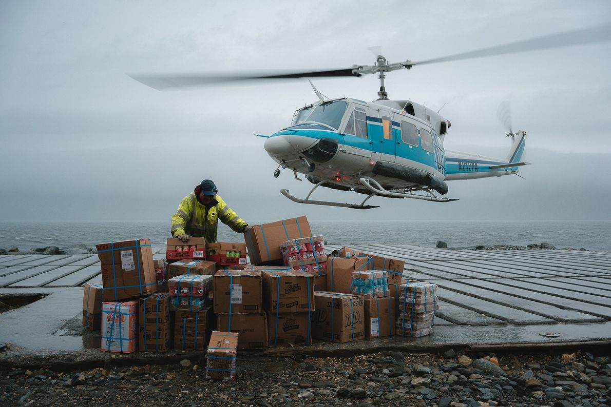 Henry Soolook, the 'chopper guy' holds down the supplies while the helicopter takes off back to ...