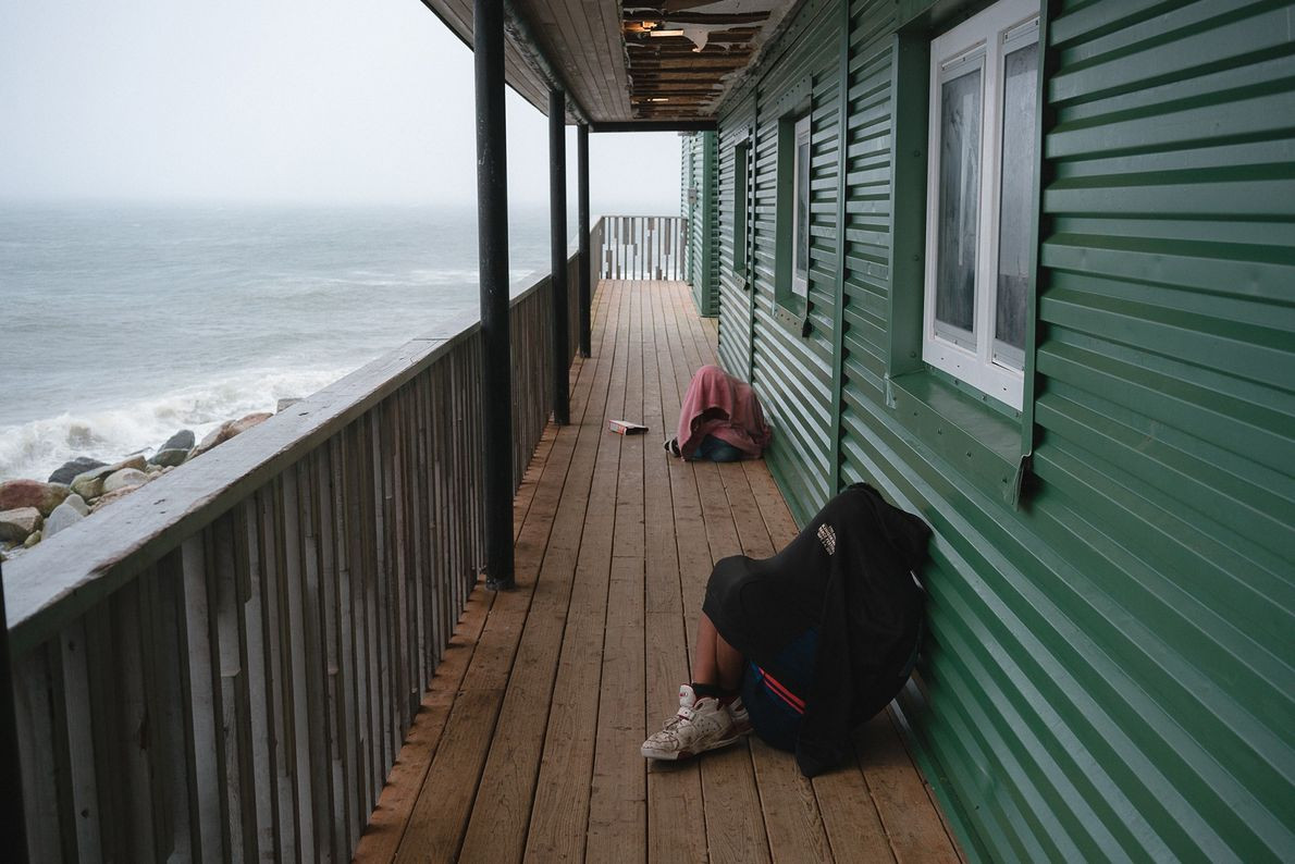 Teenagers huddle on the school porch to get Wi-Fi, which is turned on every afternoon (often ...