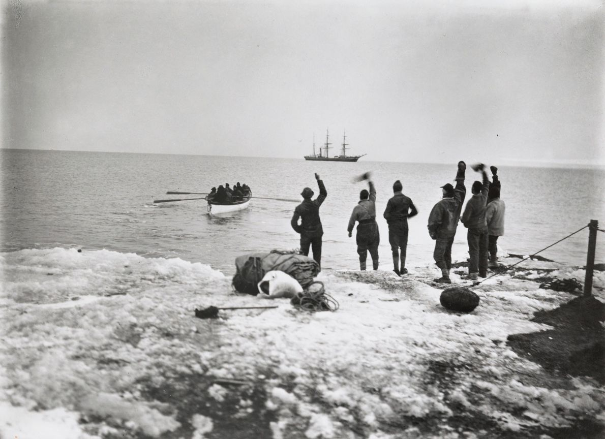 Members from Robert Falcon Scott's polar expedition stand on the shore and wave to departing comrades. ...