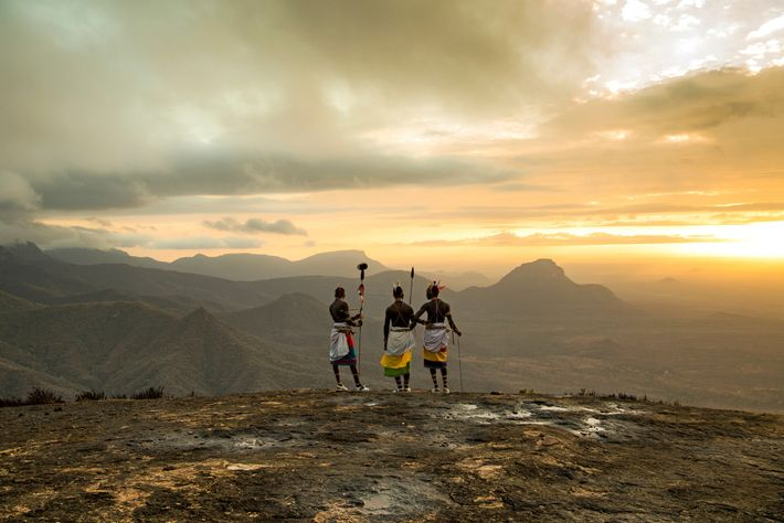 Samburu warriors stand on a ridge surrounded by the scrubby grasslands of the Namunynak Wildlife Conservation ...
