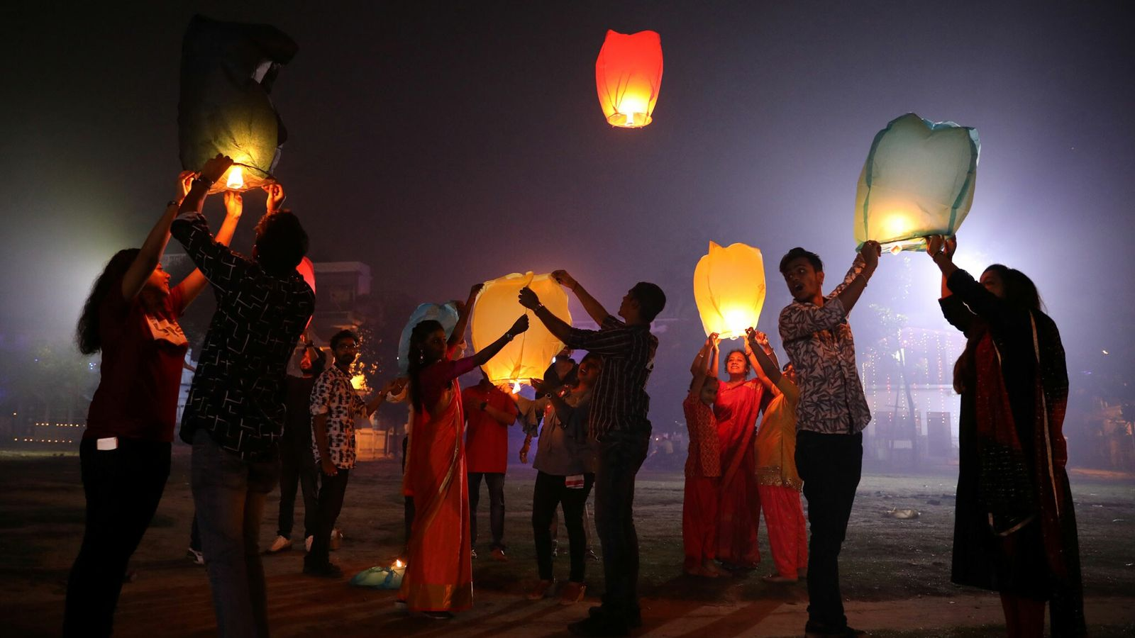 People gather to release sky lanterns in celebration of Diwali—India's five-day festival of lights—in the town ...