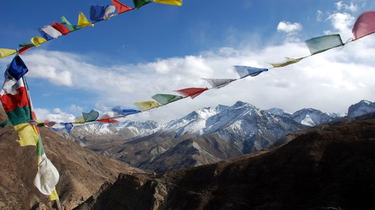 Buddhist prayer flags wave at the top of a high pass in western Nepal.