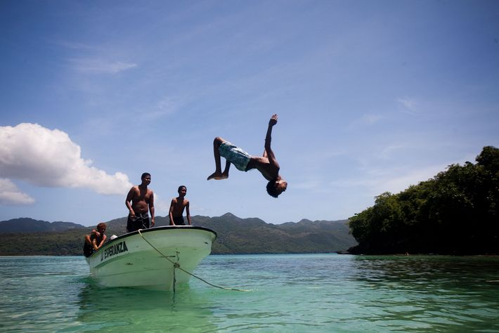 A local backflips off the bow of a boat into the clear waters off the Samaná ...