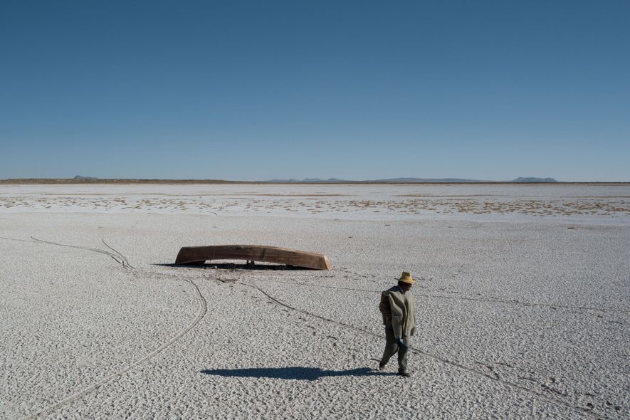 The bed of Bolivia's dry, salt-crusted Lake Poopó unfurls into the distance. Boats are stranded; the ...