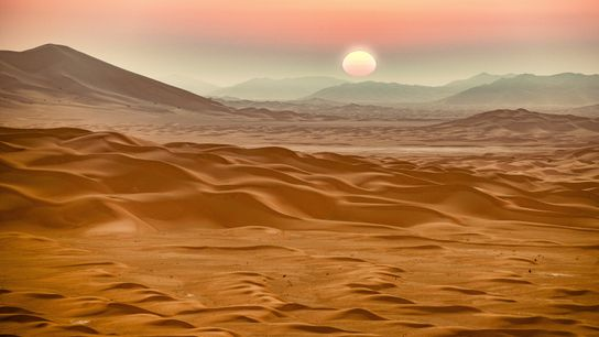 As the sun rises over the desert in the Rub' al Khali (Empty Quarter), myriad colours wash ...