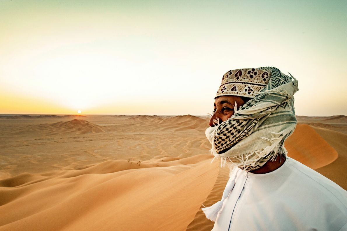 Desert guide Musallam Ahmed shields himself as sand grains are thrown into the air by desert ...