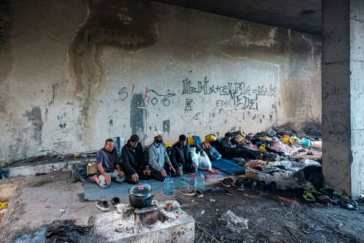Muslim migrants take a moment to pray in an makeshift encampment where they live while tracing ...