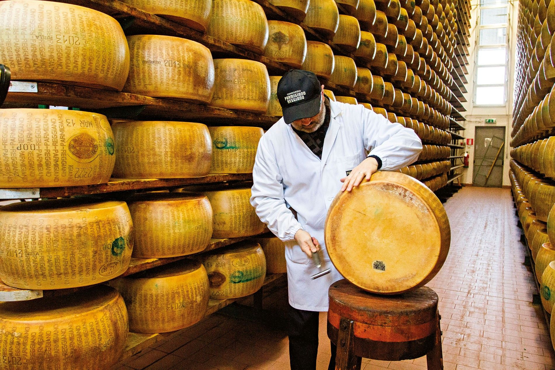 A master grader at Italy's Parmigiano-Reggiano Consortium tests the quality of a wheel of Parma's famed ...