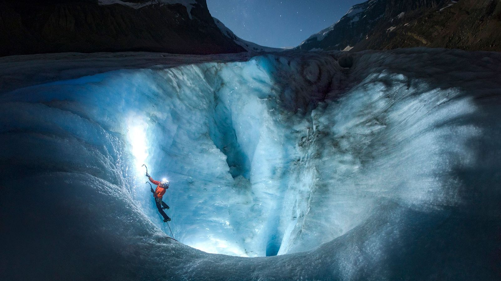 Under a night sky, an ice climber thwacks his way up the ice of Athabasca Glacier, ...