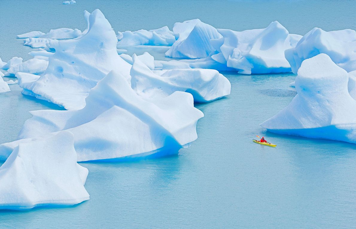 A kayaker paddles near incredible icebergs in Lago Gray, Torres del Paine National Park, Patagonia, Chile, ...