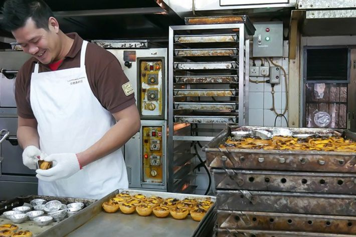 Making custard egg tarts at Lord Stow's Bakery