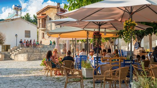 Street cafes with tourists in Omodos village, known for its production of wine.