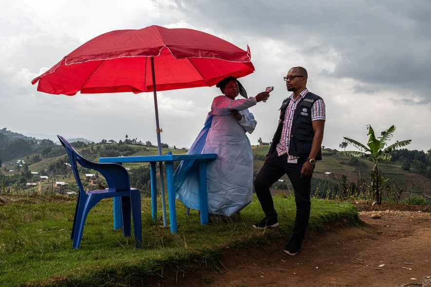 Health workers check the temperature of everyone who enters the Vayana clinic outside of Kyondo, DRC. ...