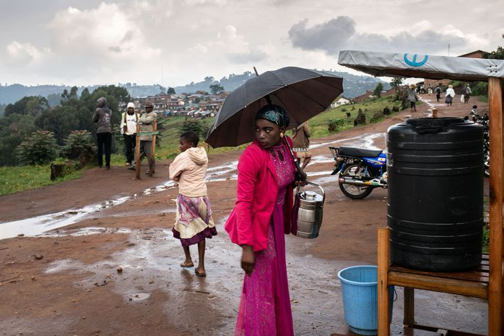 A woman washes her hands with a chlorine solution upon leaving the hospital in Kyondo, DRC. ...