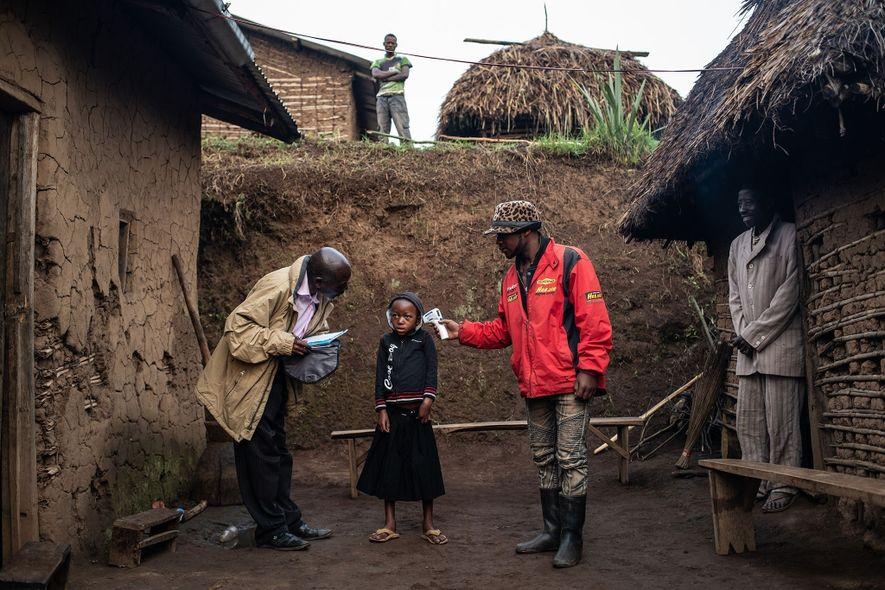 A World Health Organisation team checks the temperature of Confirme Masika Mughanyira, 7, in Vayana town, ...