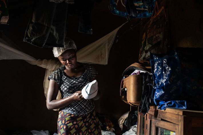 Ebola survivor Aisha Ramzani Djadi, 17, holds up clothing she had gathered to prepare for her ...