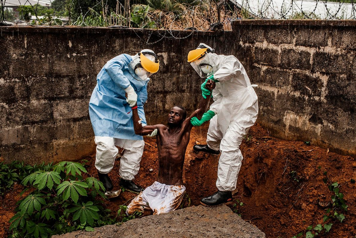 Medical staff at the Hastings Ebola Treatment Centre in Sierra Leone escort a man in the ...