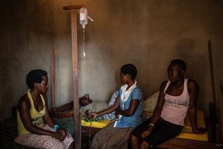 Three sisters sit with their 14-year-old brother Kakule Kavendivwa, a suspected Ebola case, in a private ...
