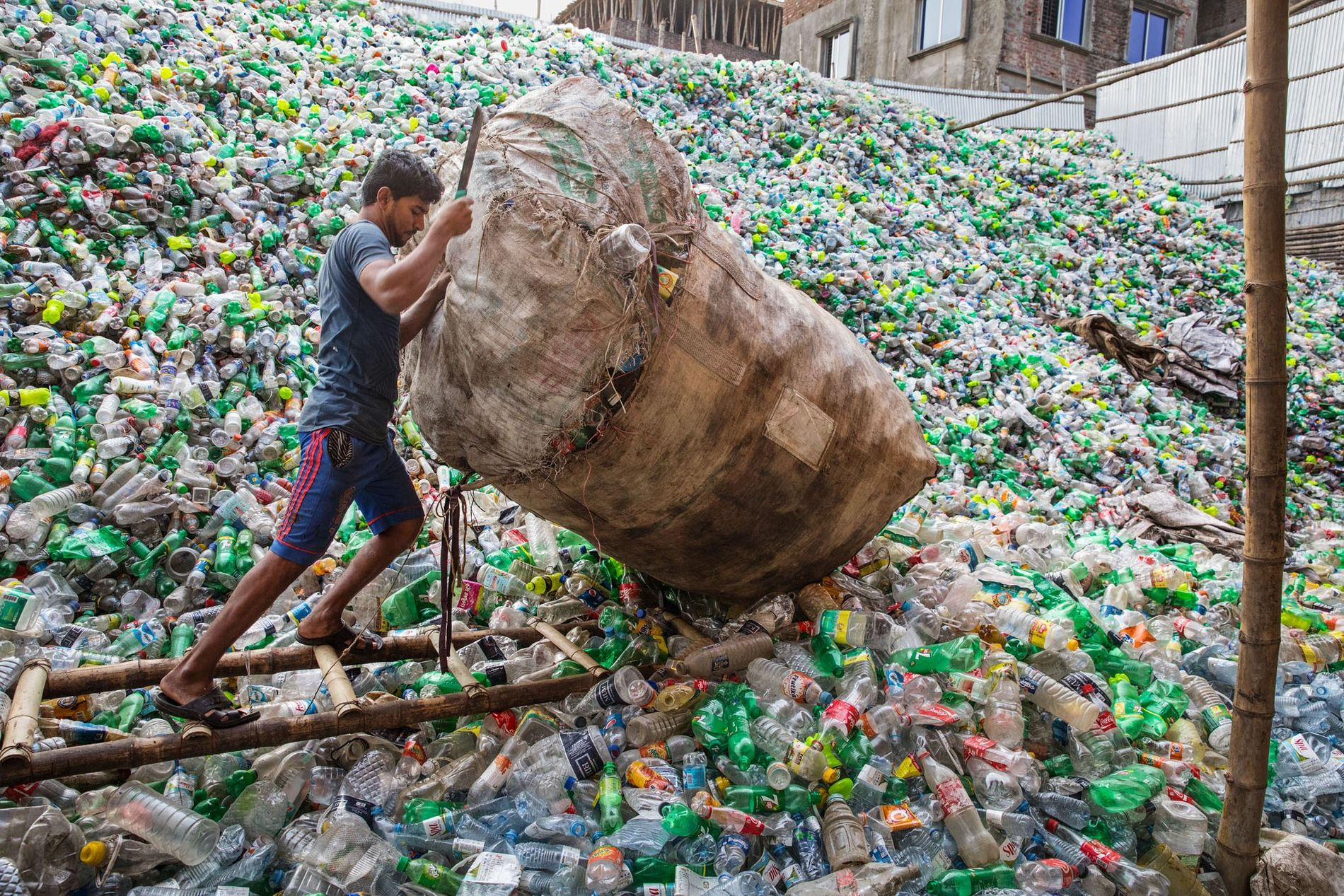 In Dhaka, Bangladesh, a man adds to a mountain of discarded plastic bottles. With the June 2018 issue, National Geographic invites other institutions to join us in reducing plastic use. Watch out for updates.