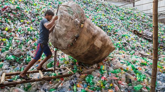 In Dhaka, Bangladesh, a man adds to a mountain of discarded plastic bottles. With the June ...