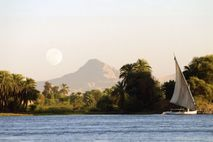 A felucca vessel moors on the river banks under a moonrise.