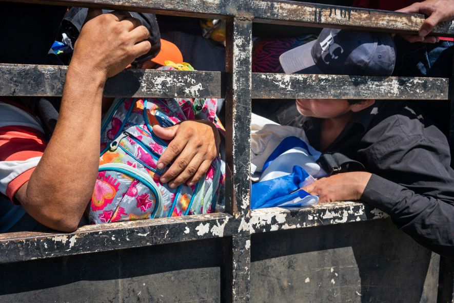 Salvadoran immigrants pack into trucks offering rides on the way to the Guatemala border on October ...