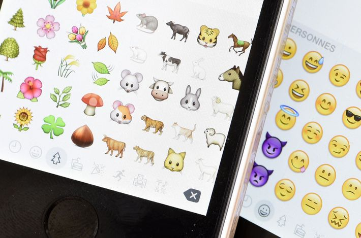 Emoji characters also known as emoticons on the screens of two mobile phones in Paris on ...