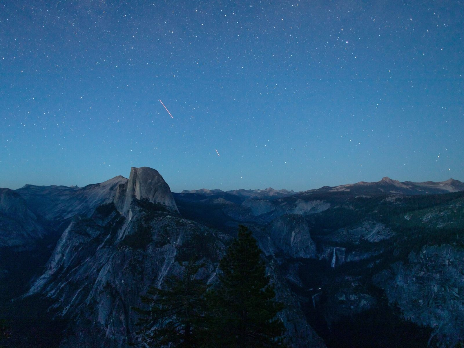 Dusk falls over Yosemite Valley's natural attractions, including Half Dome (center left) and Nevada Fall (lower ...