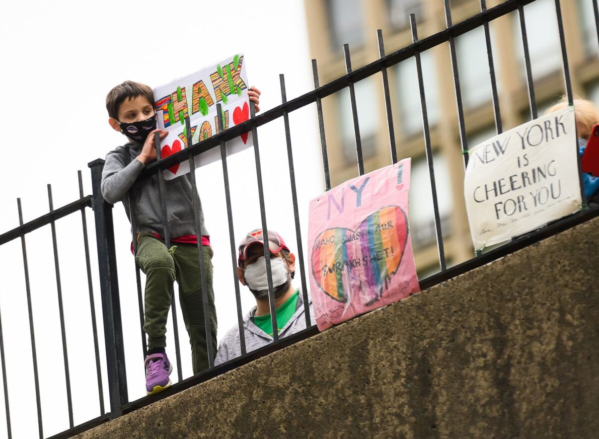 A boy holds up a thank-you sign to medical staff and essential workers near New York ...