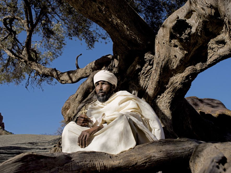 The resident priest of Abuna Yemata Guh rests under a sacred olive tree before embarking on ...