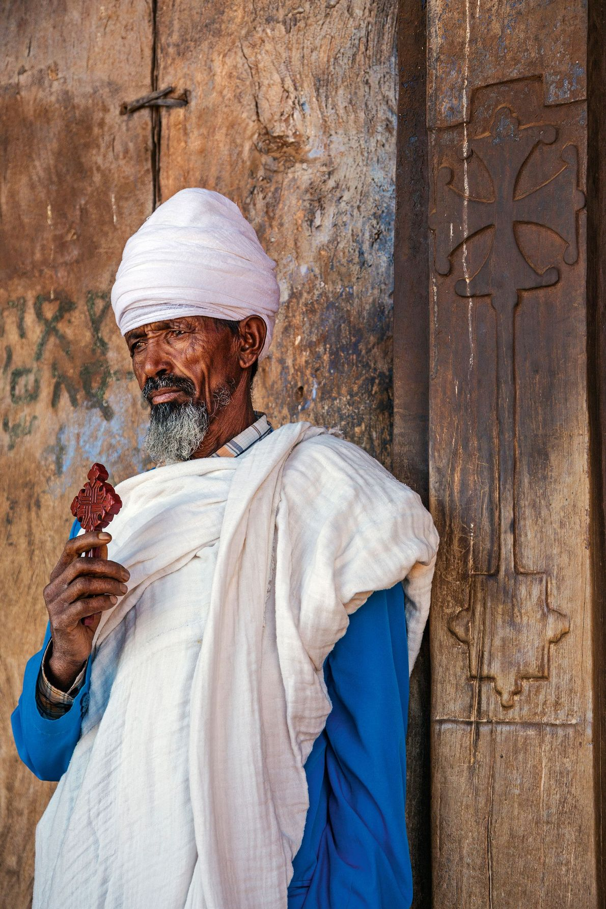 A Coptic priest outside the huge wooden doors of the semi-monolithic 10th century church of Abraha ...