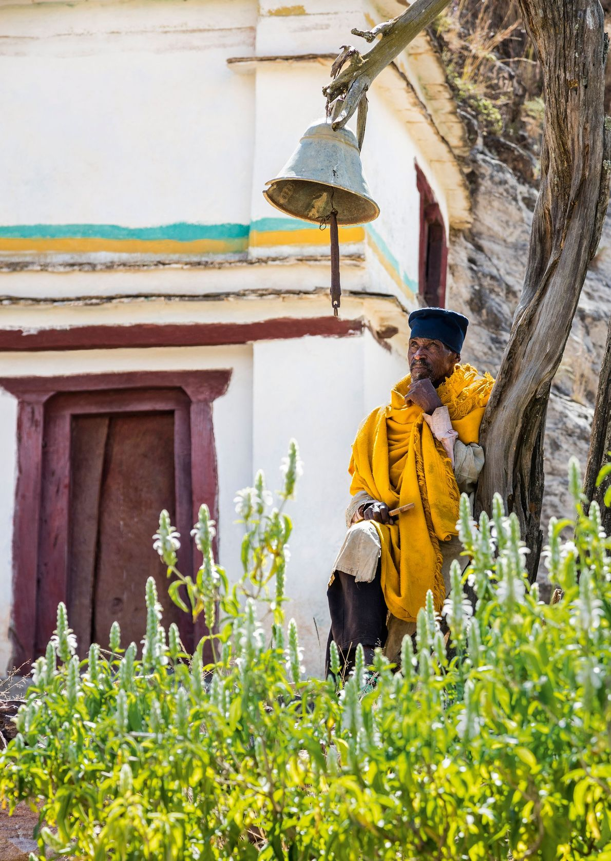 A priest sits beneath the church bell outside the rock-hewn church of Maryam Korkor.