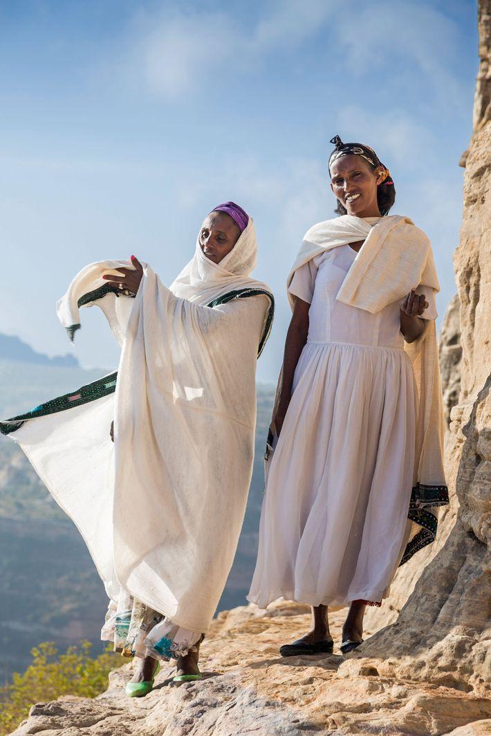 Two Tigrayan women walk along a narrow ledge towards the ancient rock-hewn church of Abba Daniel ...