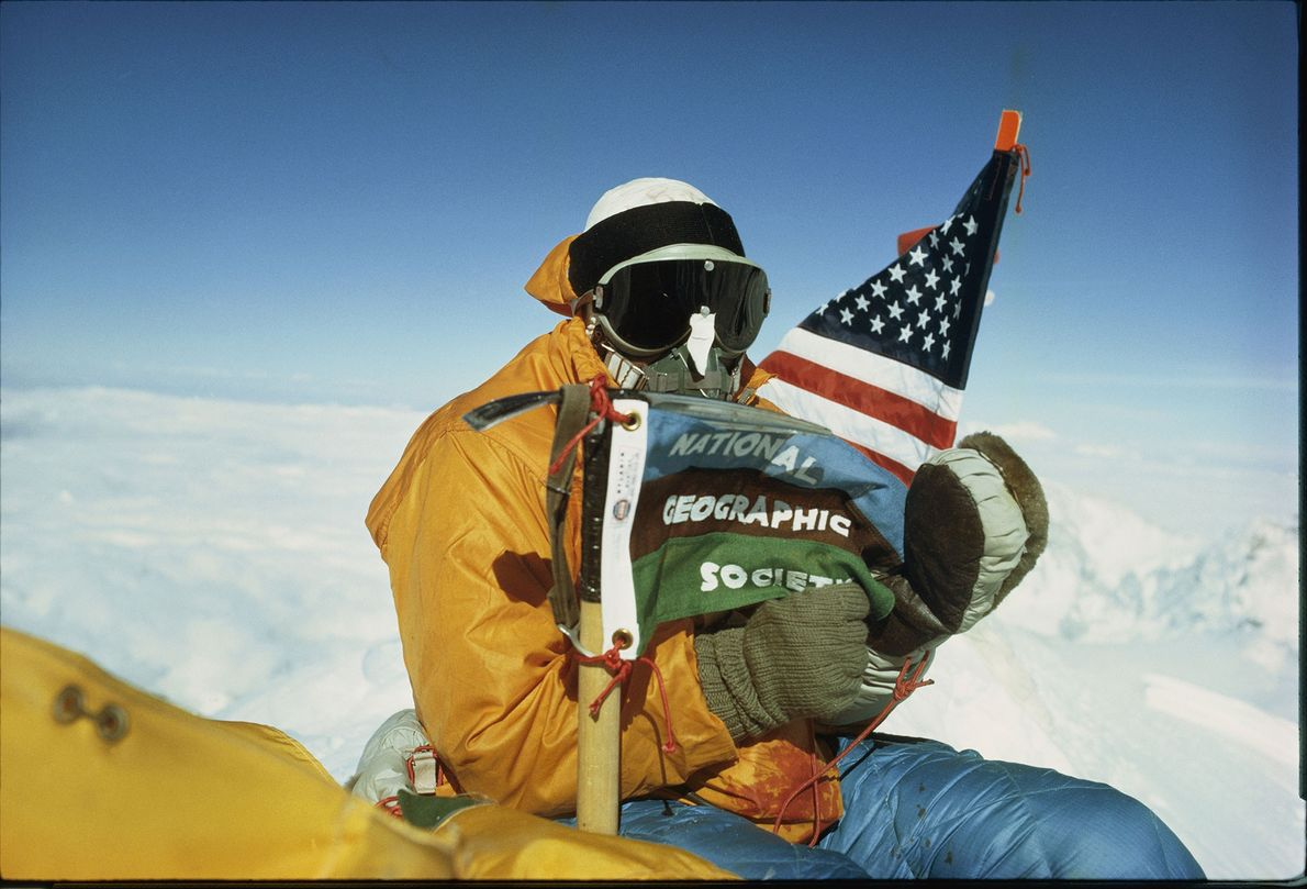 Barry Bishop holds the American flag and the flag of the National Geographic Society at Mount ...