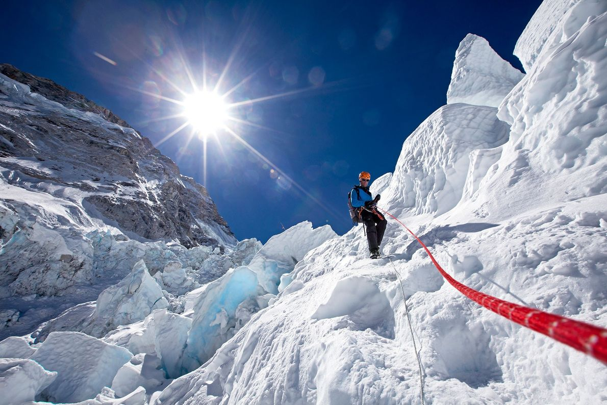 Conrad Anker uses a fixed rope to guide himself safely down an ice step in the ...