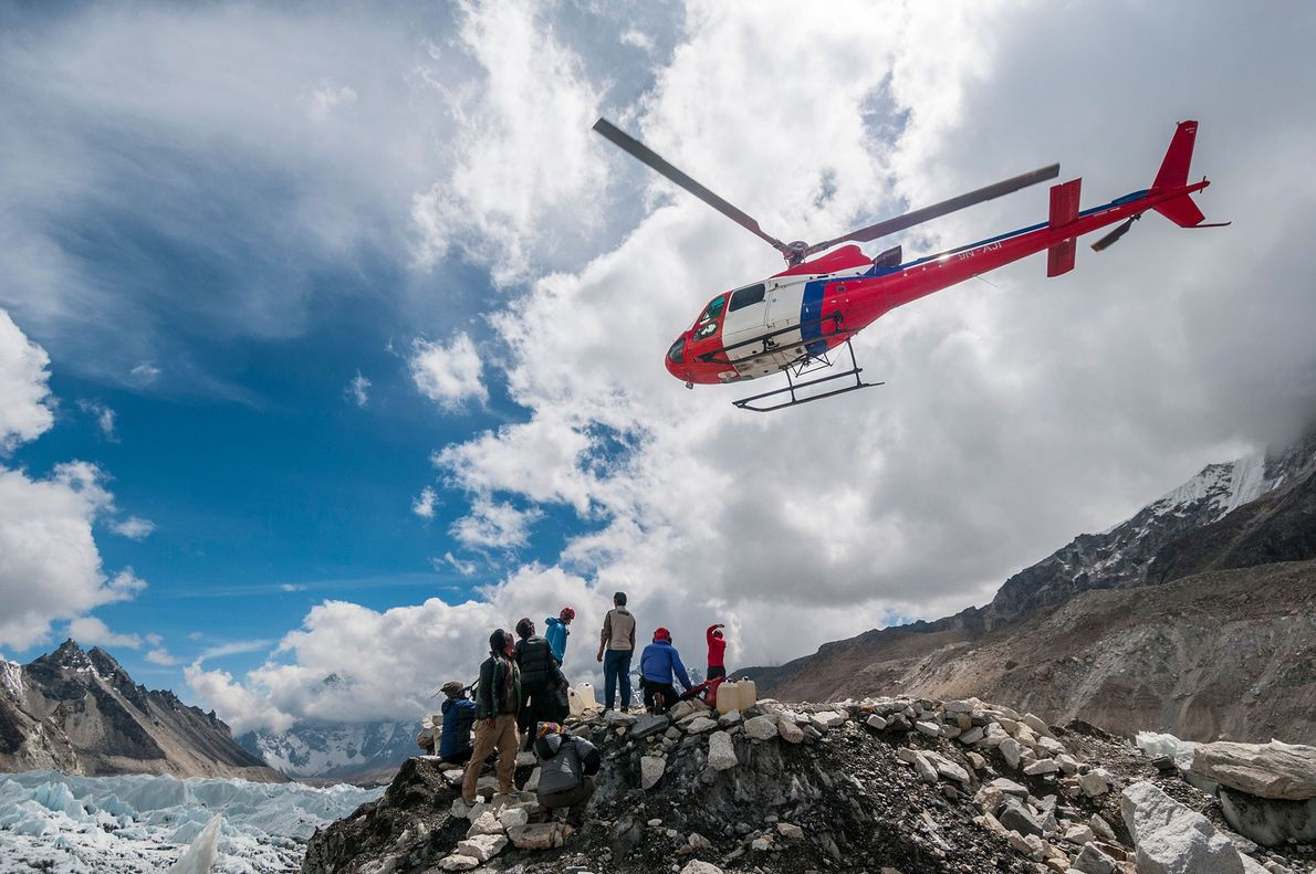 Helicopters take off from and land at the helipad on Everest Base Camp while rescuing injured ...