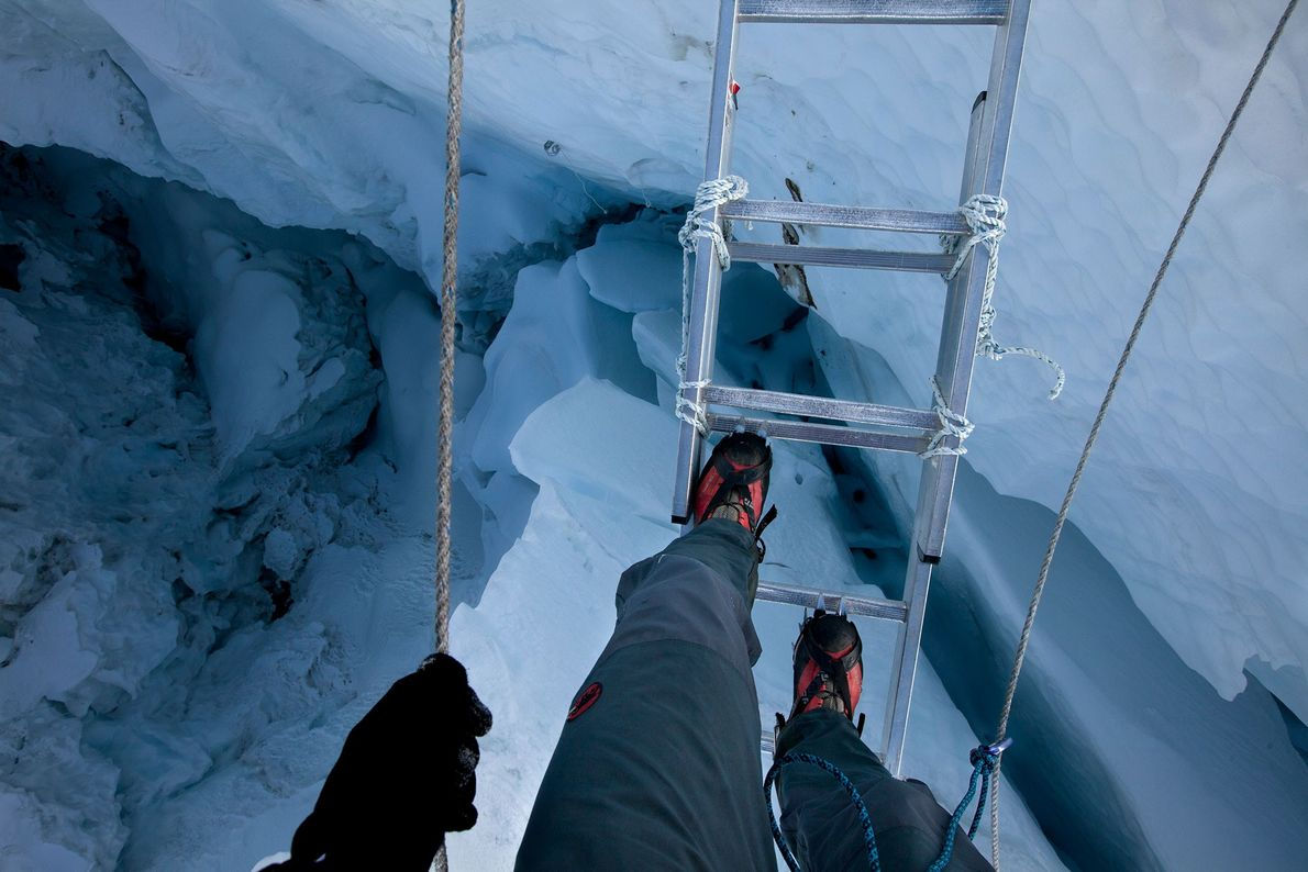 On a 2012 expedition, a climber crosses a crevasse in the Khumbu Icefall by using a ...