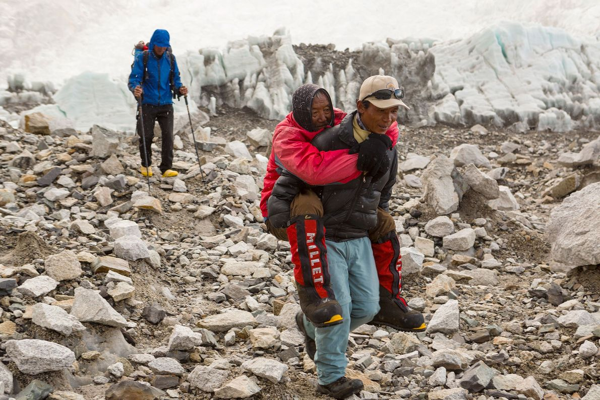 A sherpa rescues an 82-year-old Nepali man attempting to climb Everest in 2013.
