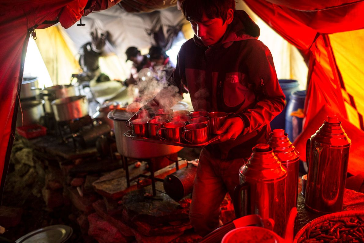 A man carries a tray filled with warm drinks through a camp kitchen at Everest Base ...