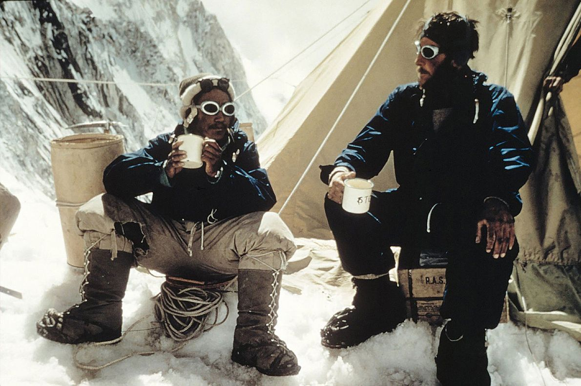 Tenzing Norgay and Edmund Hillary drink a celebratory cup of tea after their successful ascent of ...